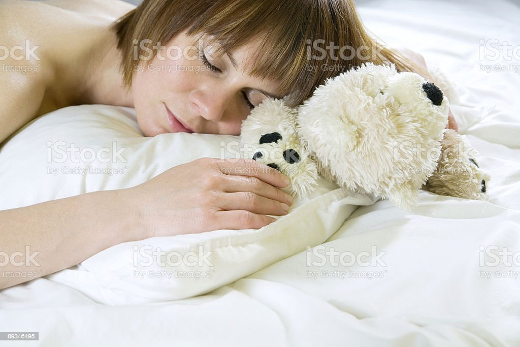 Sleeping young woman with her teddy bear royalty-free stock photo