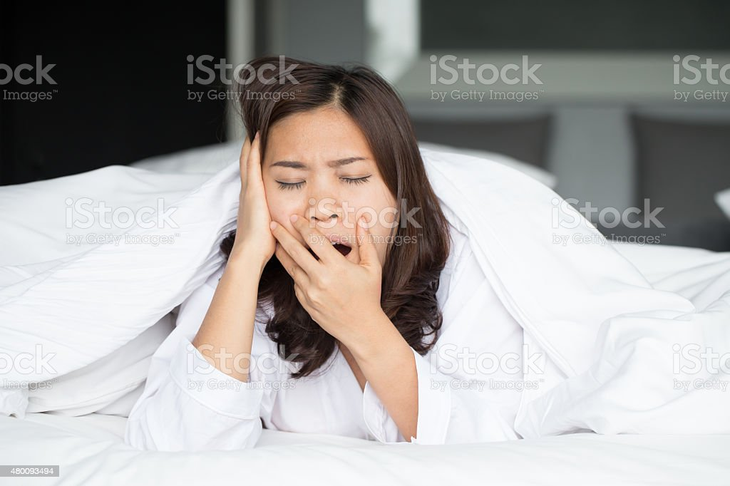 Sleepy asian woman yawning in bed at home stock photo