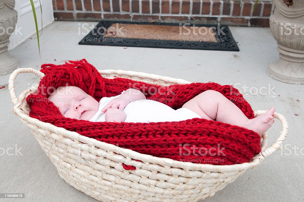Sleepy Baby girl left on a door step stock photo
