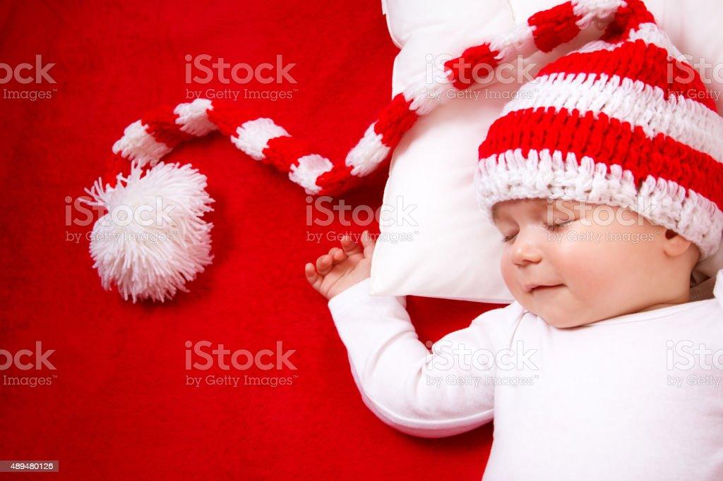 Sleepy baby on red blanket stock photo