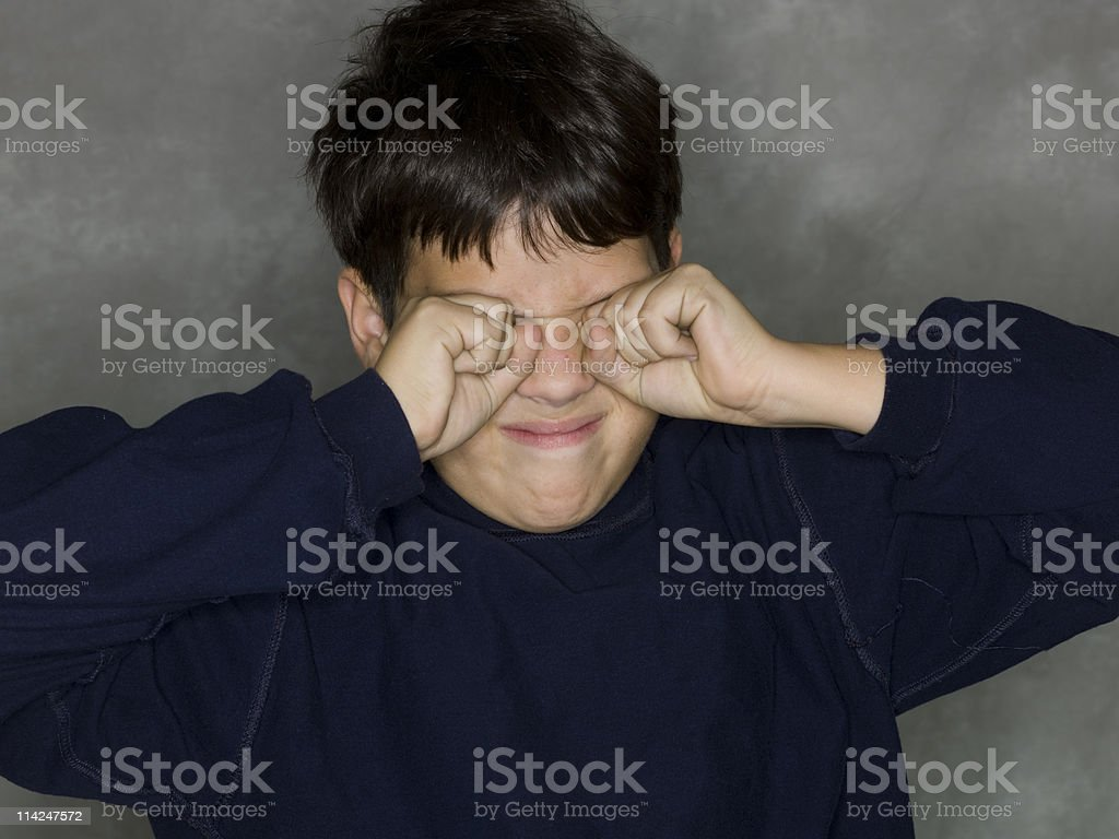 A sleepy boy running his fisted hands over his eyes. royalty-free stock photo