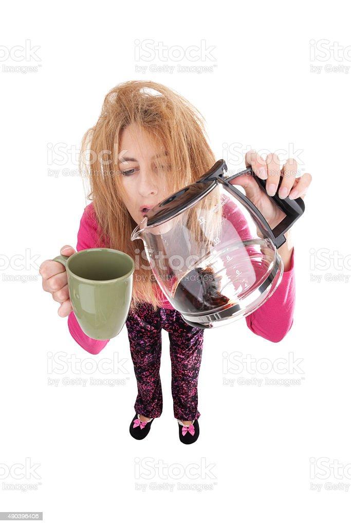 Sleepy Fisheye Woman In Pajamas Pouring Coffee stock photo