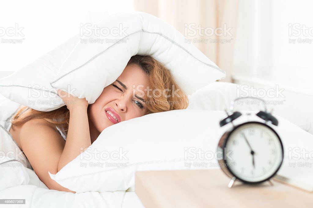 Sleepy girl looking at alarm clock and trying to hide stock photo