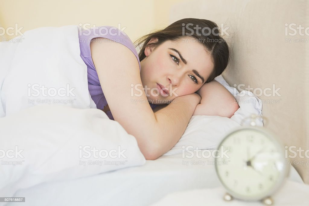 Sleepy girl waking up in her bed stock photo