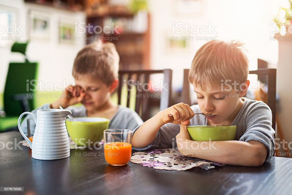 Sleepy little boys eating breakfast cereal stock photo