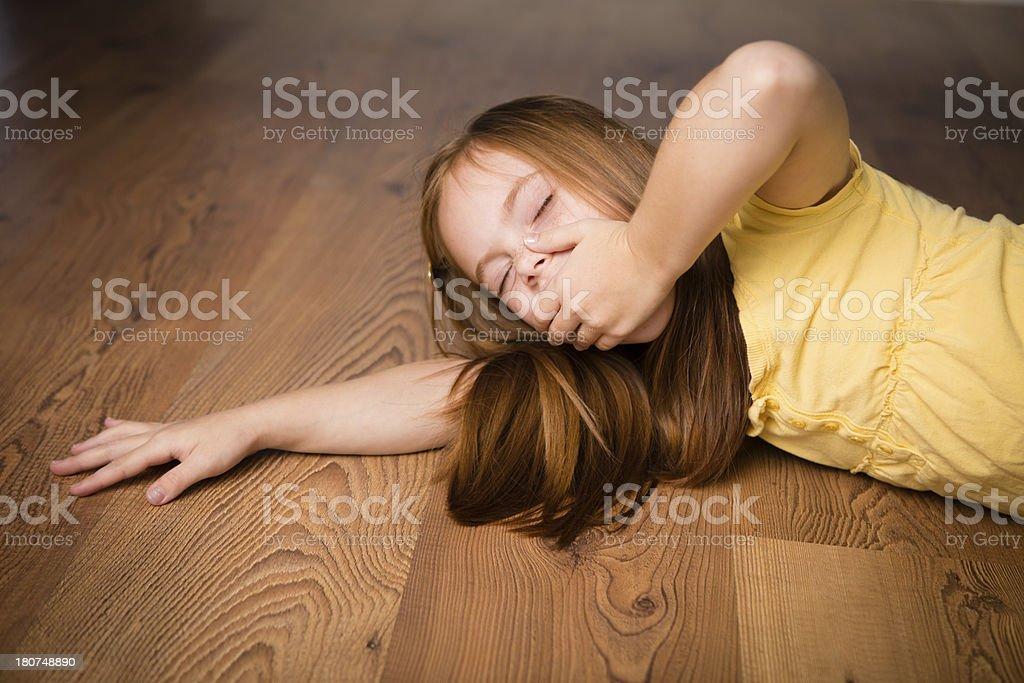Sleepy Seven Year Old Girl Lying on Floor royalty-free stock photo