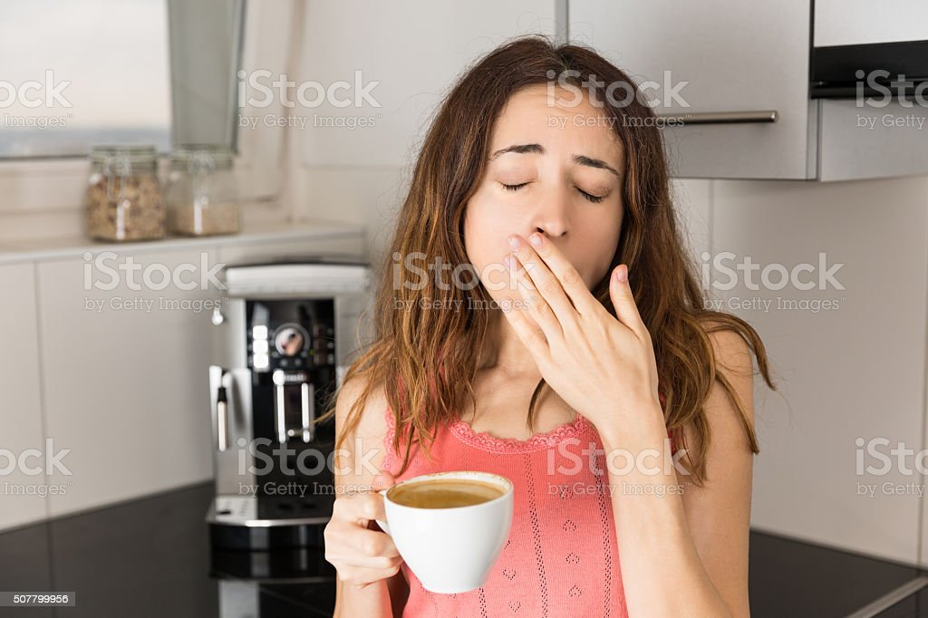Sleepy woman in the morning drinking coffee stock photo