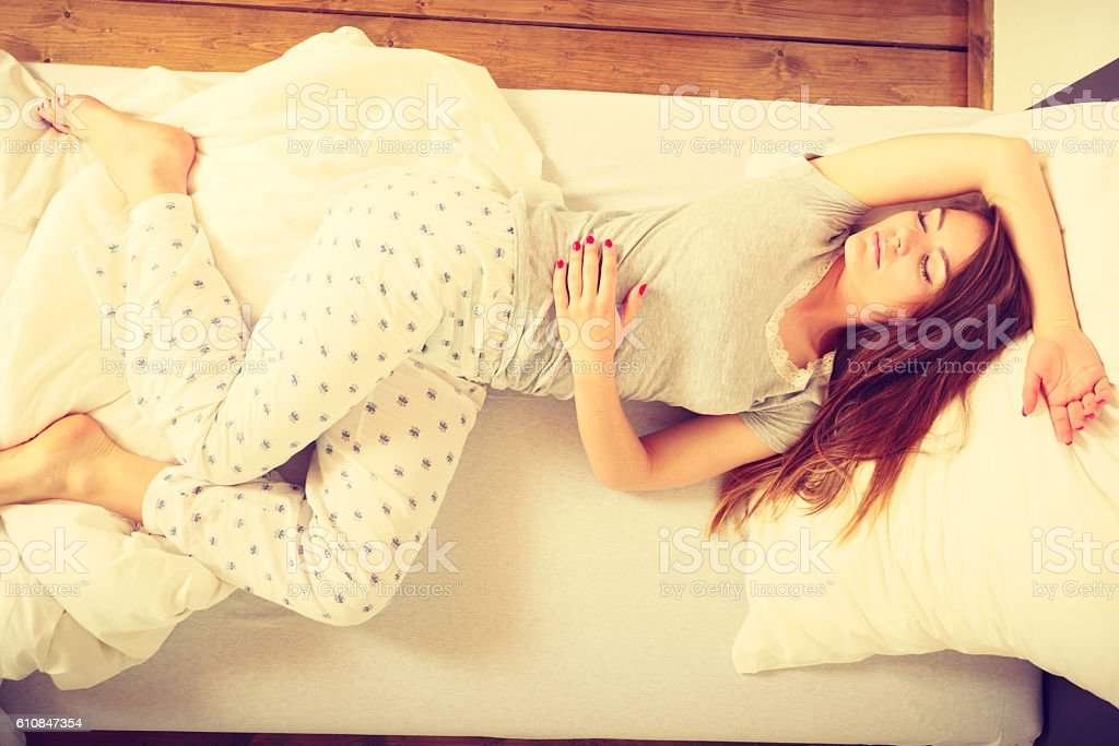 Sleepy woman sleeping in the bed. stock photo