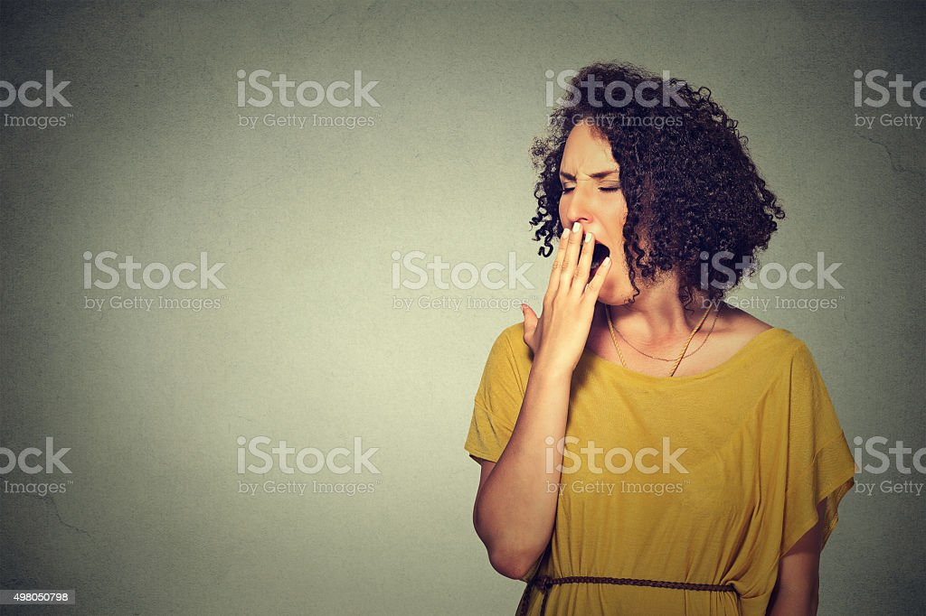 sleepy woman with wide open mouth yawning looking bored stock photo