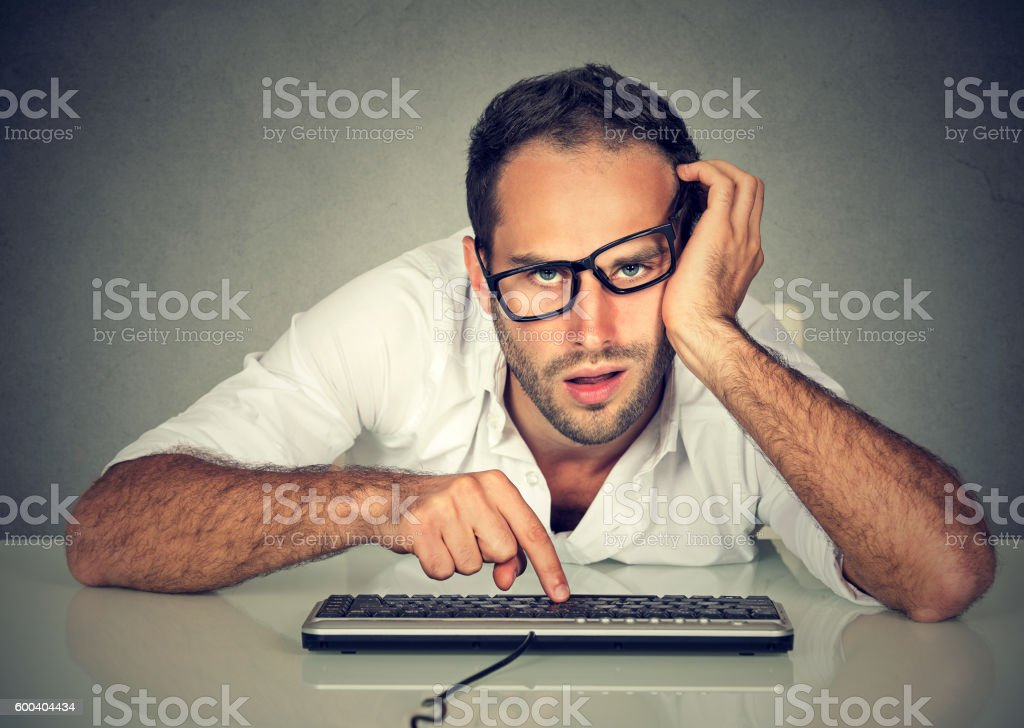 Sleepy worker young man working on computer stock photo