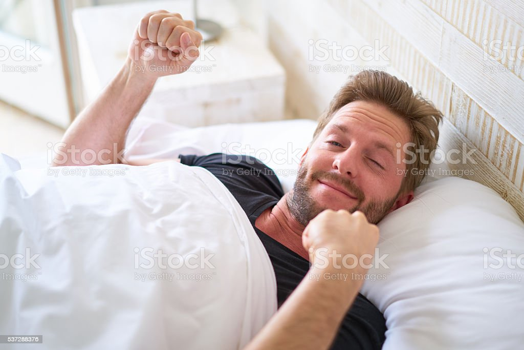 sleepy young man just after waking up stock photo