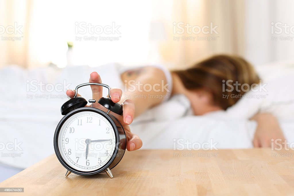 Sleepy young woman trying kill alarm clock stock photo