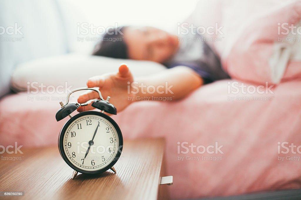 Sleepy young woman trying kill alarm clock stock photo