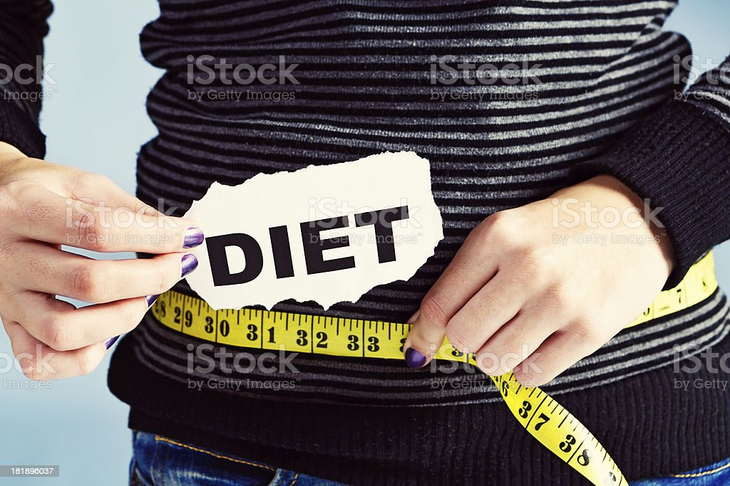 Slender woman with DIET sign measures hips, possibly anorexic? royalty-free stock photo
