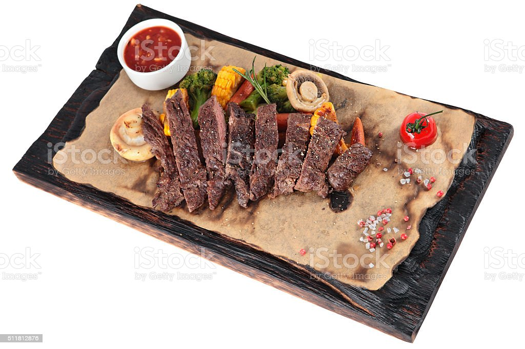 Slice into pieces fried Skirt steak with vegetables on white. stock photo