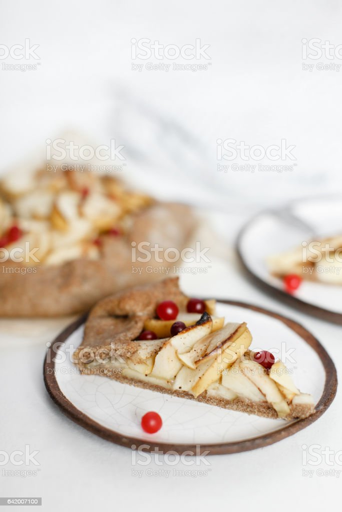 Slice of apple galette with cinnamon and cranberries on a beautiful plate stock photo
