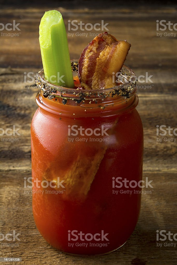 A slice of bacon dipped in Bloody Mary in a mason jar  stock photo