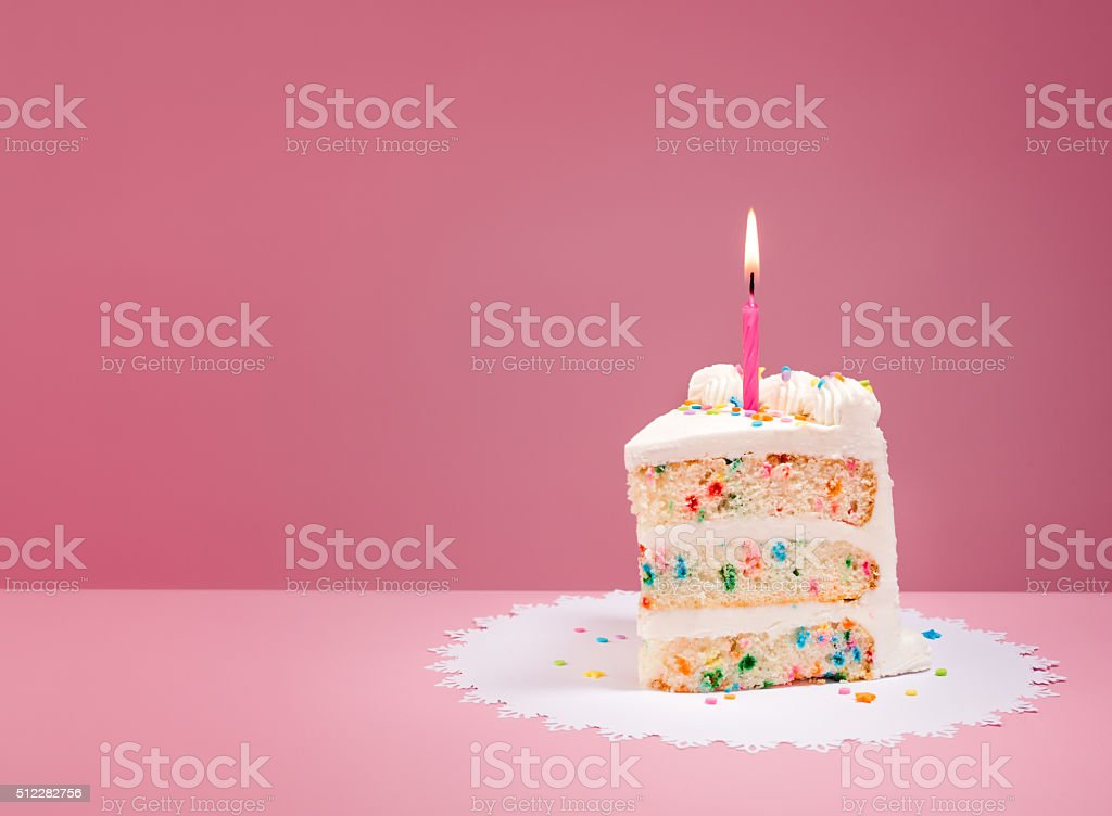 Slice of Birthday Cake with Candle on Pink stock photo