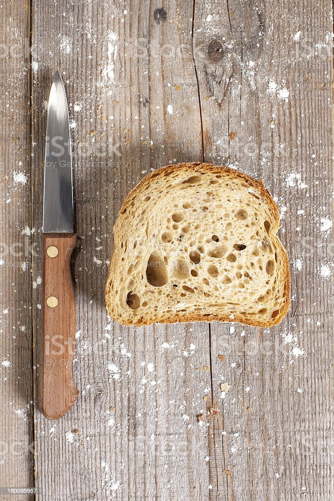 slice of bread with a knife on wooden background royalty-free stock photo