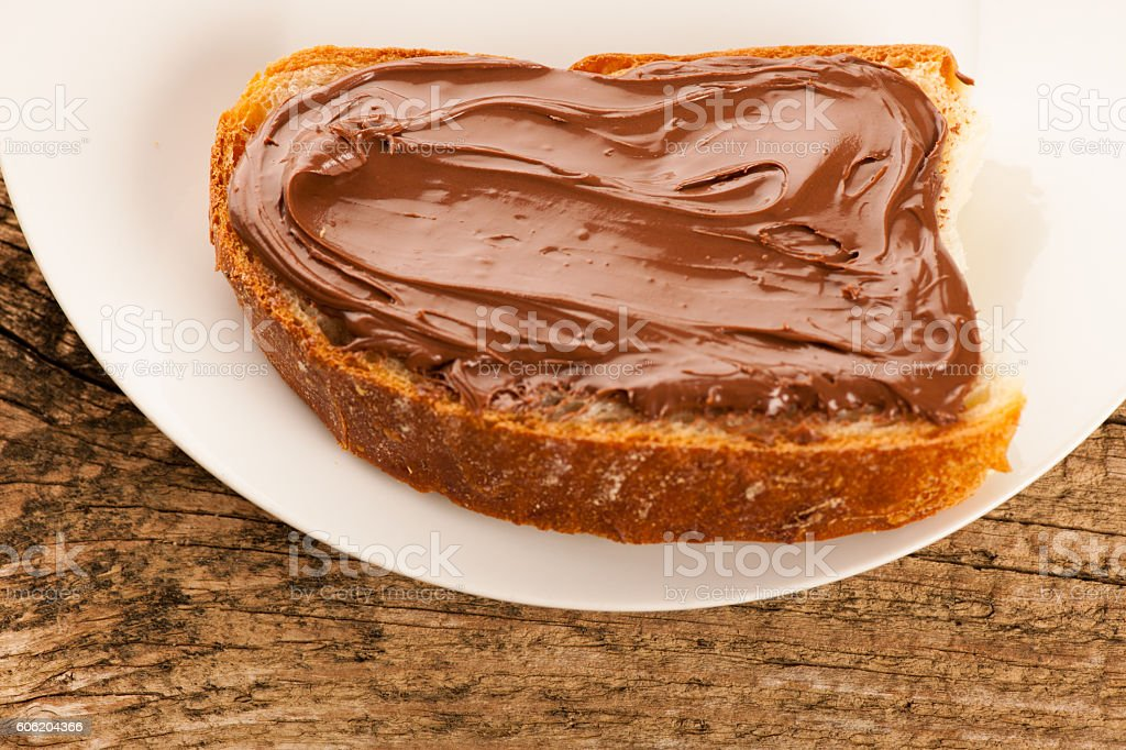Slice of bread with sweet chocolate nougat spread on plate stock photo