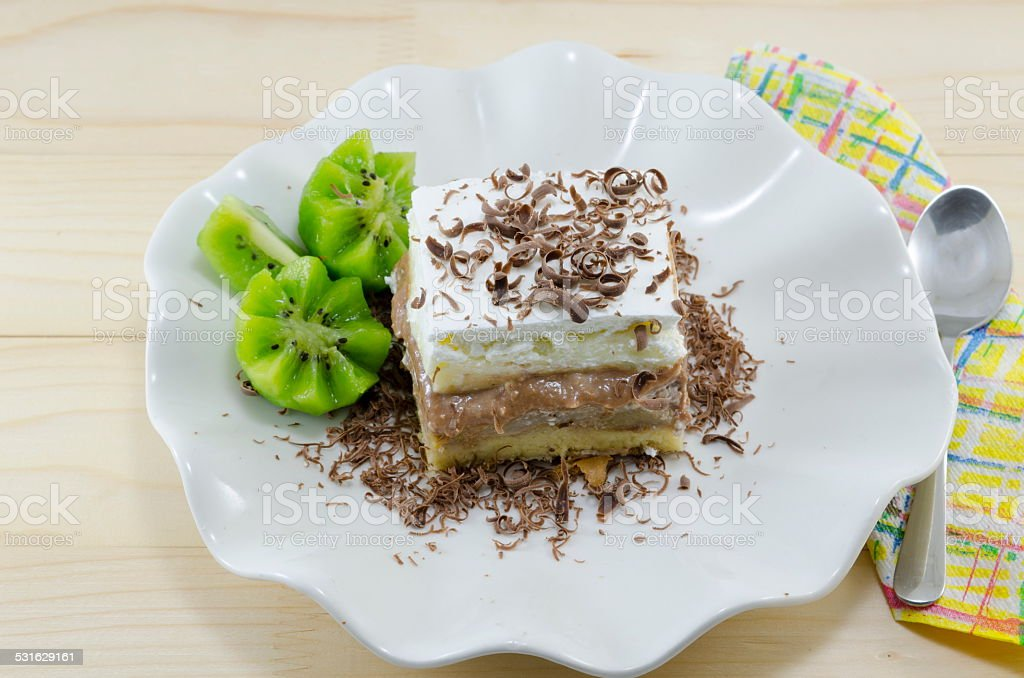 Slice of cake with kiwi garnish on a plate royalty-free stock photo