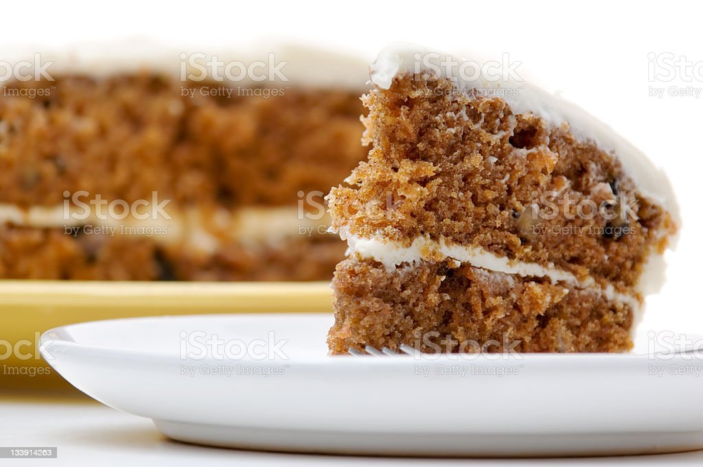 Slice of carrot cake on white plate in front of blurred cake stock photo
