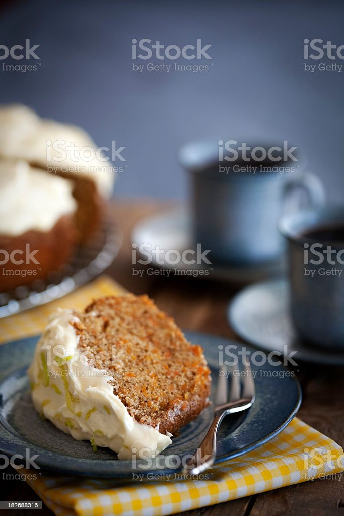 Slice of carrot cake served with coffee in blue plate ware royalty-free stock photo