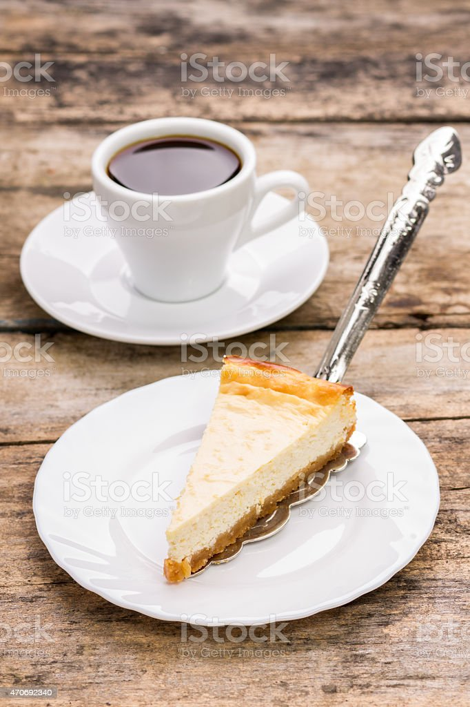 Slice of cheesecake on plate with cup of coffee stock photo