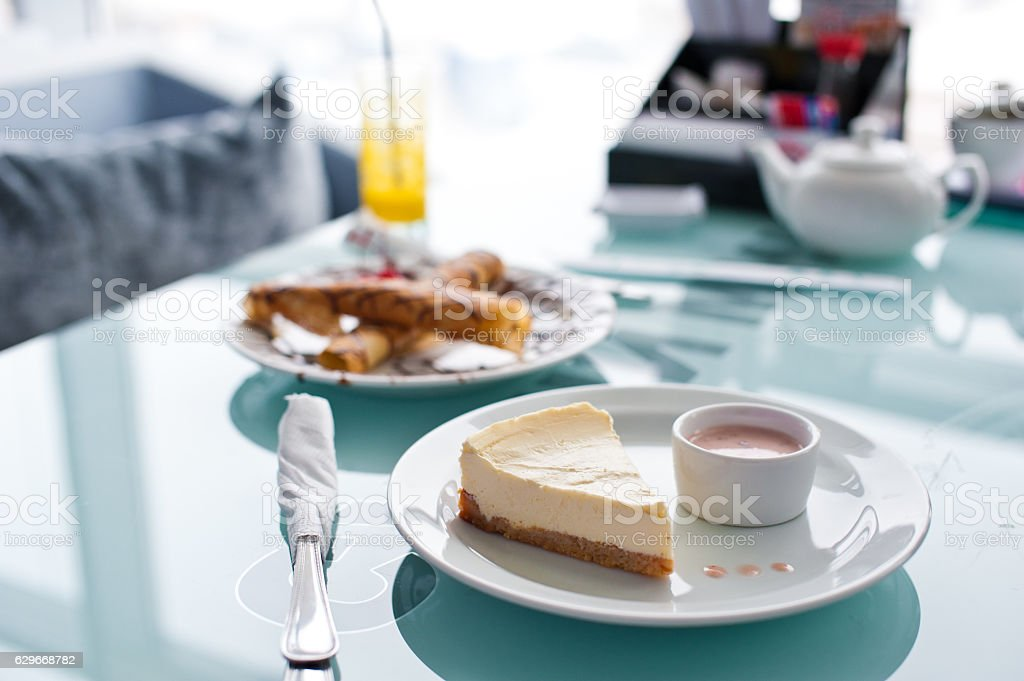 Slice of cheesecake on white plate and glass table in stock photo