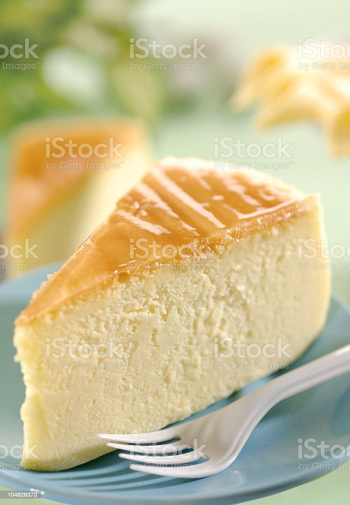 Slice of cheesecake with a plastic fork on a blue plate stock photo
