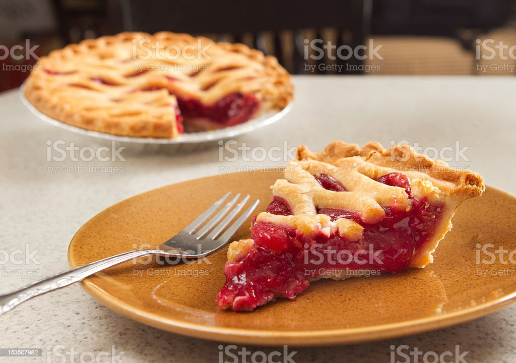 A slice of cherry pie on a brown plate with a fork stock photo