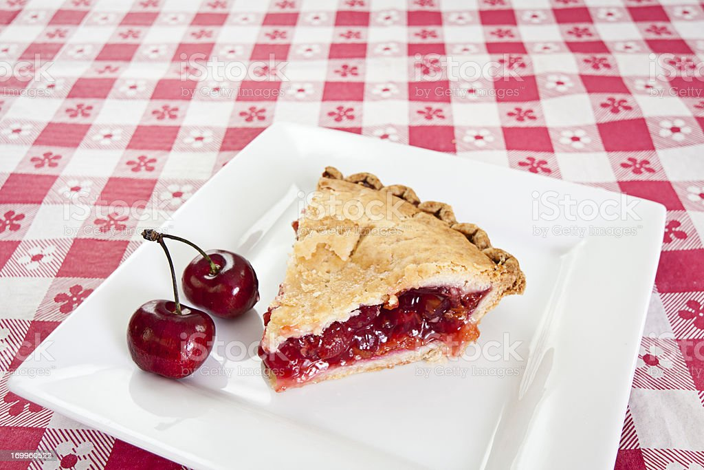 Slice of cherry pie with cherry on side on plate stock photo