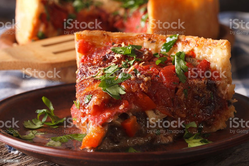 Slice of Chicago deep dish pizza on plate macro. Horizontal stock photo