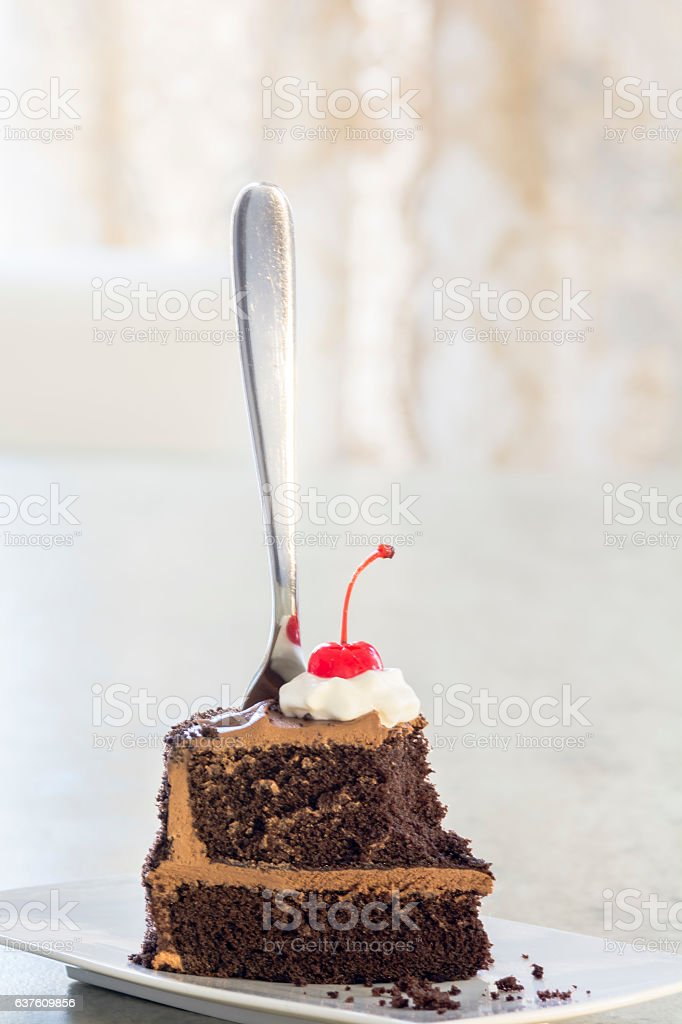 Slice of chocolate cake with a cherry on top. stock photo