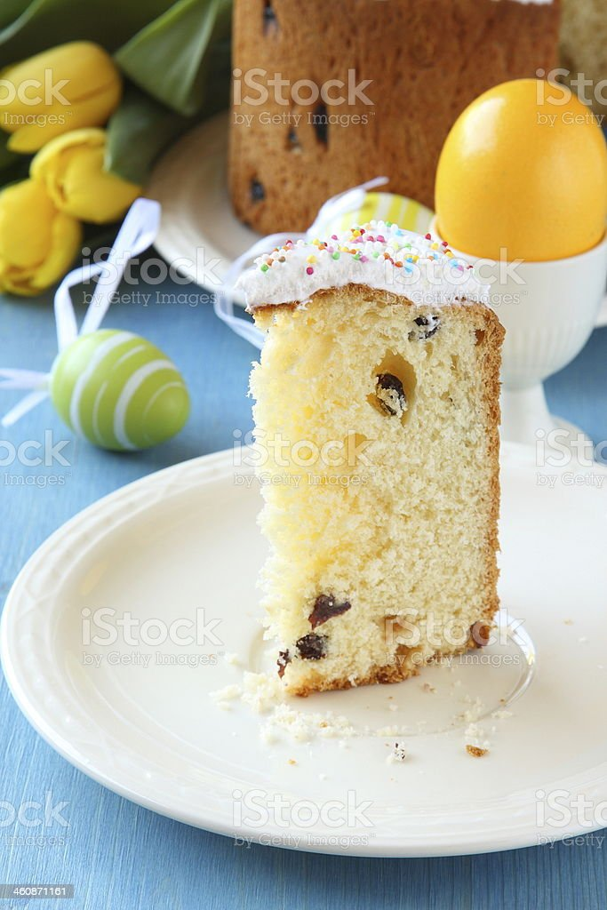 Slice of easter bread with colorful eggs and yellow tulips stock photo