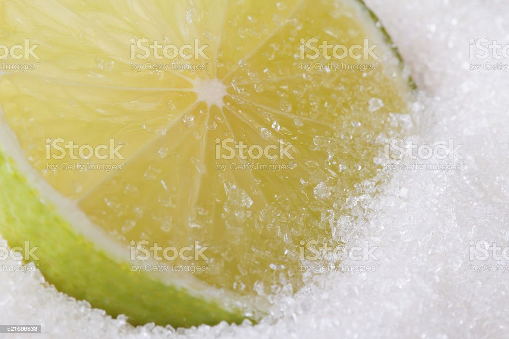 Slice of fresh lime in sugar closeup stock photo