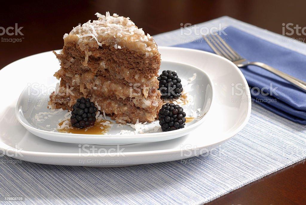 Slice of German Chocolate cake with blackberries royalty-free stock photo