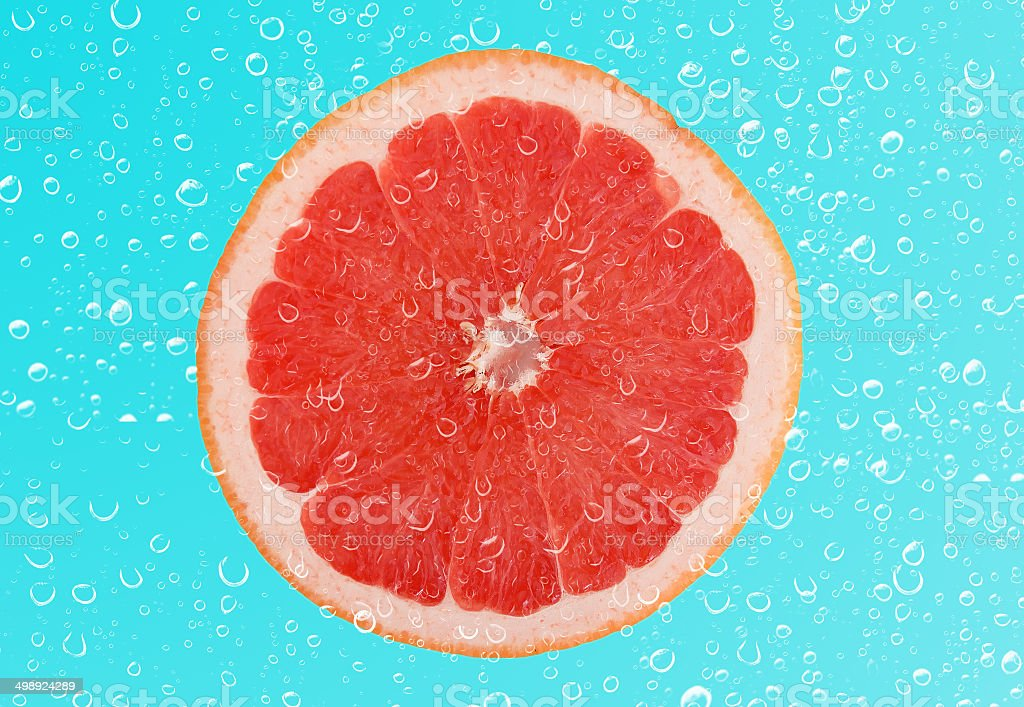 Slice of grapefruit with drop on blue background royalty-free stock photo