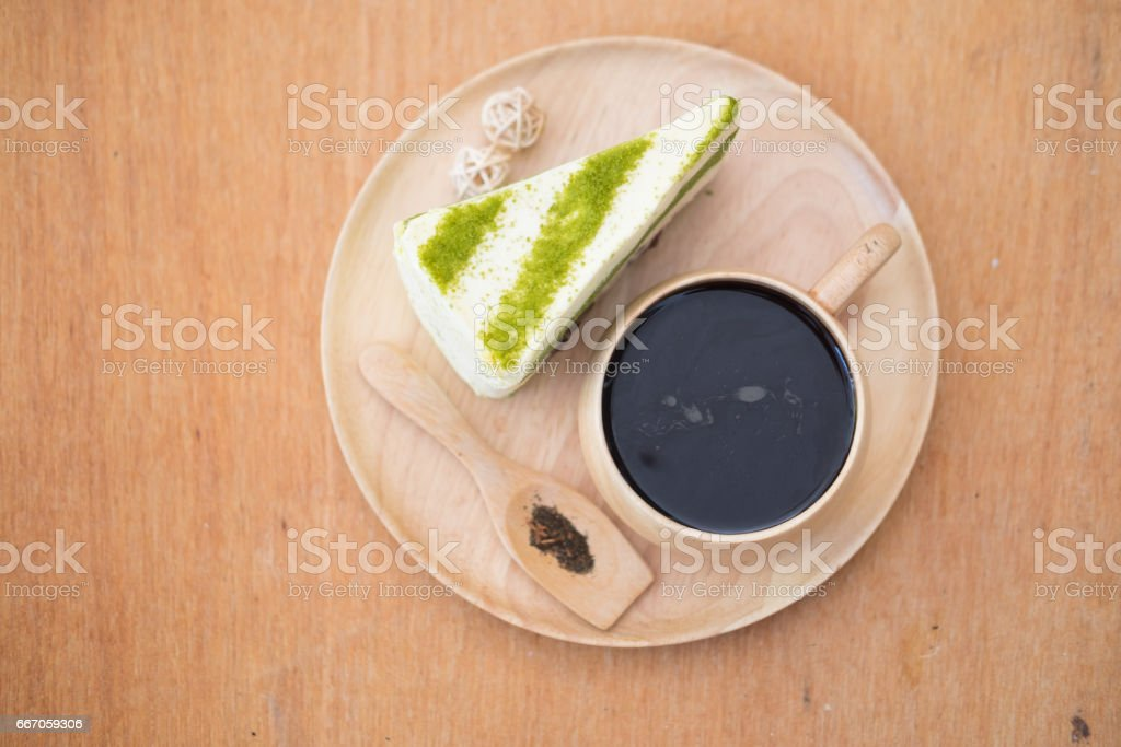 Slice of green tea cake with hot tea, top view stock photo