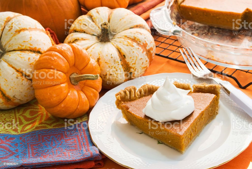 slice of homemade pumpkin pie on antique china with pumpkins stock photo