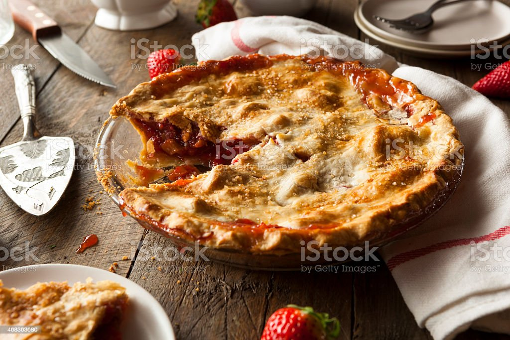 A slice of homemade strawberry rhubard pie on a wooden table stock photo