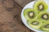 Slice of Kiwi fruit on white plate. Selective focus.