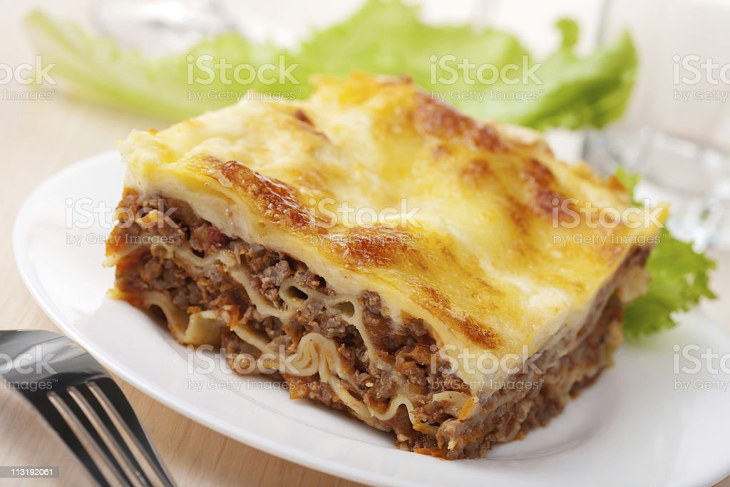 Slice of lasagna Bolognese with fresh greens royalty-free stock photo