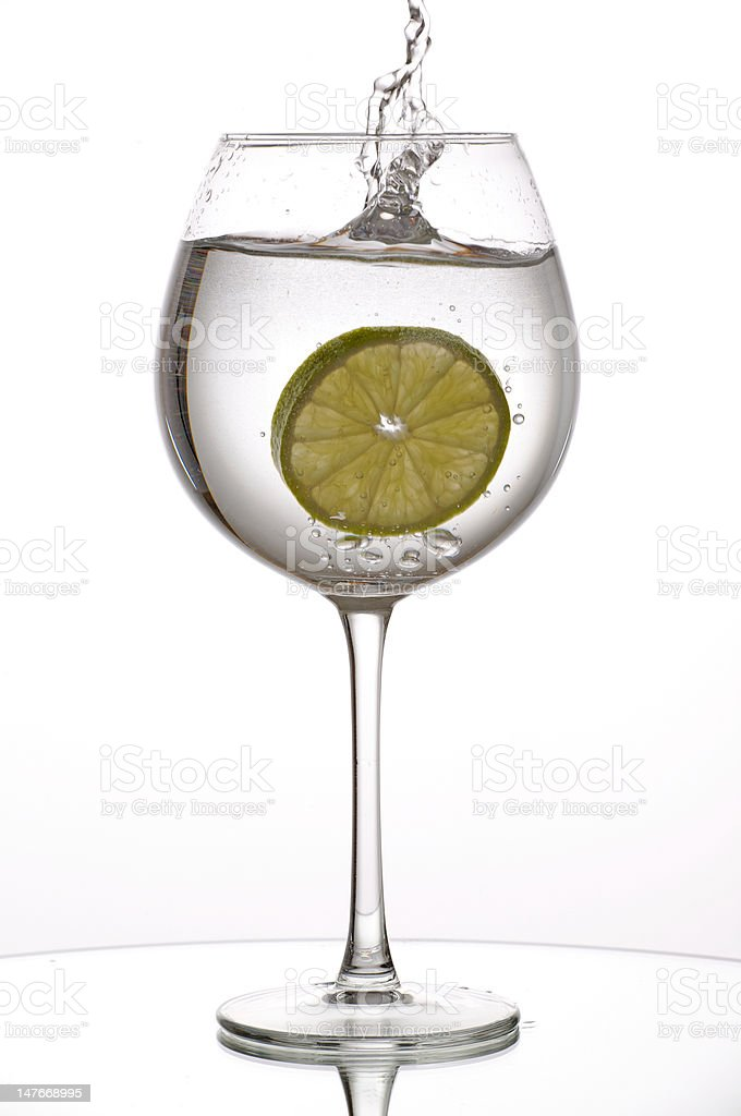 Slice of lime splashing into wine glass royalty-free stock photo