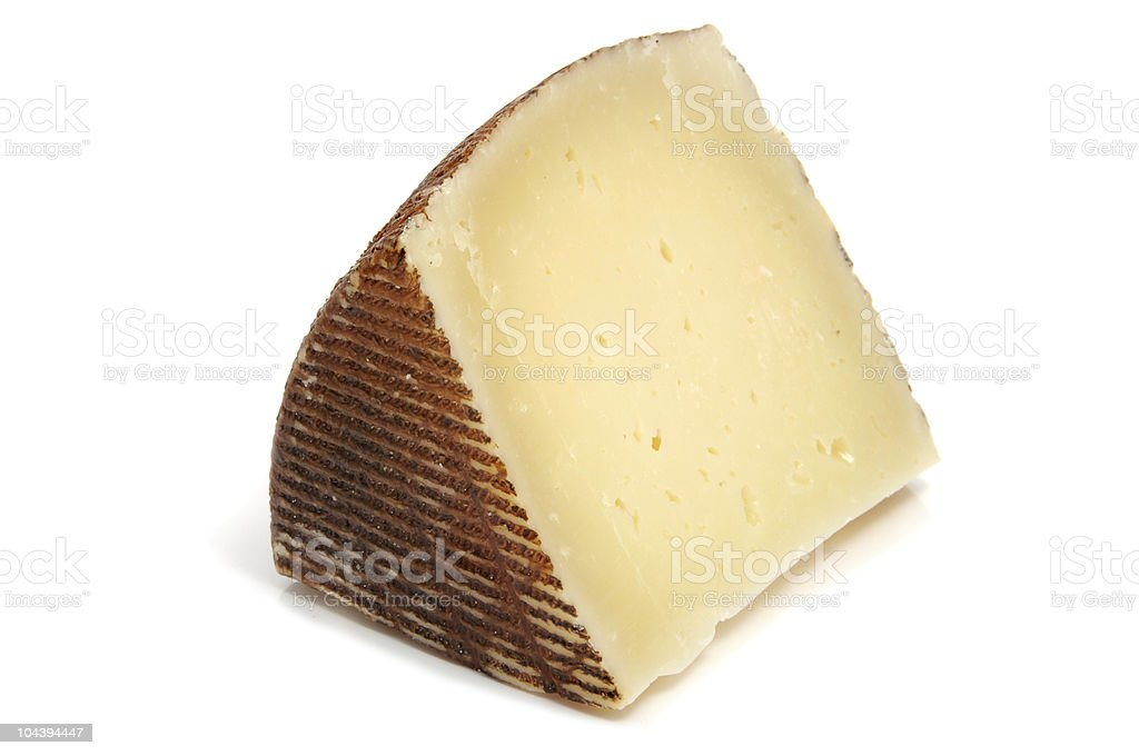 A slice of Manchego cheese with the rind on stock photo