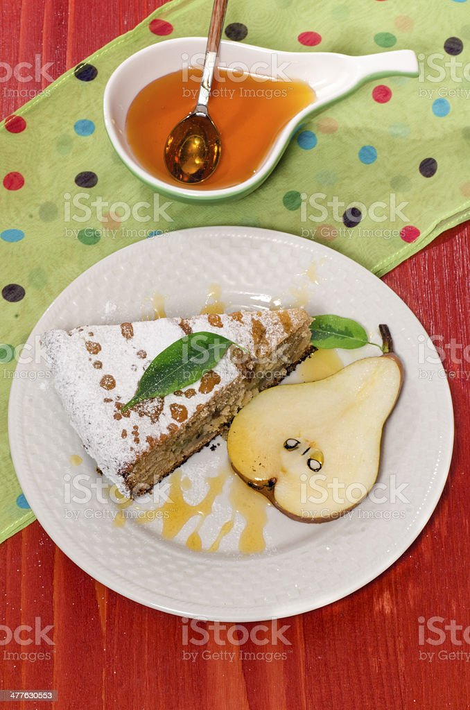 Slice of pear pie with honey on red wooden table royalty-free stock photo
