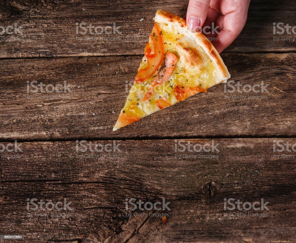 Slice of pizza in hand on dark wooden background stock photo