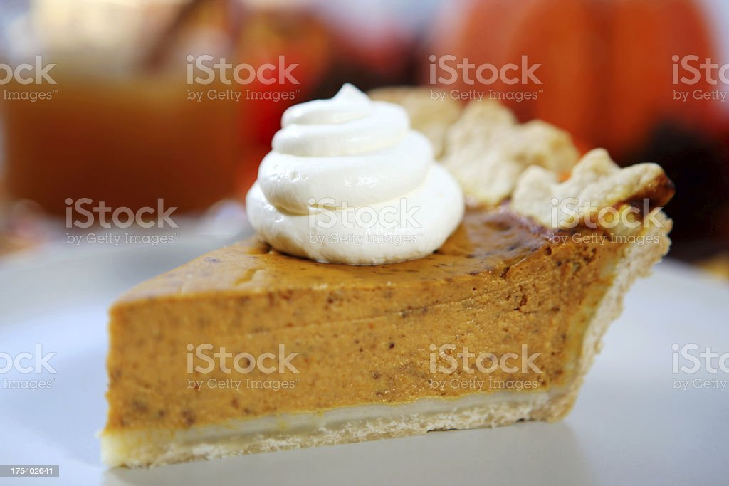 Slice of pumpkin pie with whipped cream stock photo