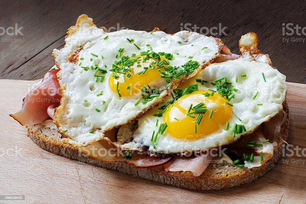 slice of rustic bread with ham  and fried eggs stock photo