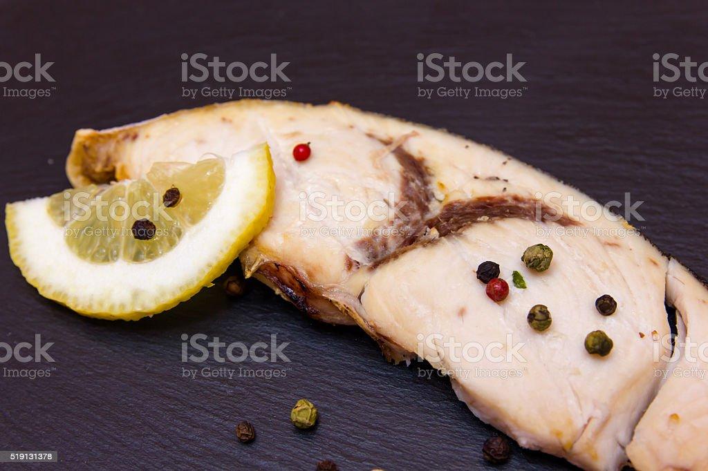 Slice of swordfish on slate close up view stock photo